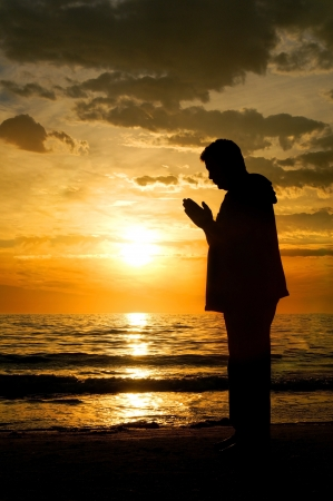 Silhouette of a man standing at the ocean praying with a beautiful sunset behind him