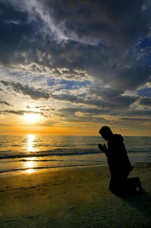 Man kneeling and praying on the beach with dramatic clouds and a golden sunset