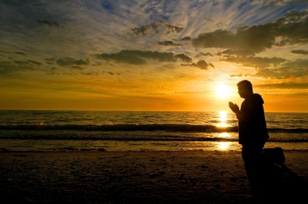 Middle aged man kneeling and praying at the beach with a glorious sunset in the background
