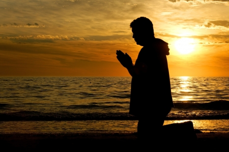 Man kneeling on the beach and praying in front of a golden sunset  Stock Photo
