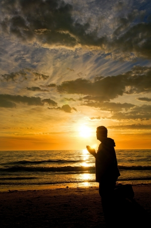 Man praying at the ocean while watching a glorious sunset  Stock Photo