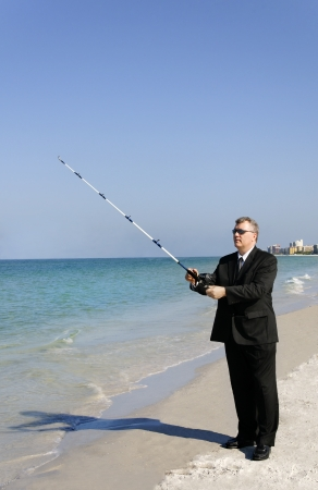 A man in a business suit fishing at the ocean.