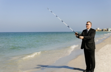 A man in a business suit fishing at the ocean with hotels in the background.