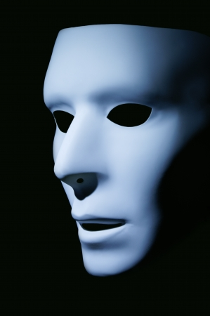 grotesque: Side view of a light blue mask taken against a black background