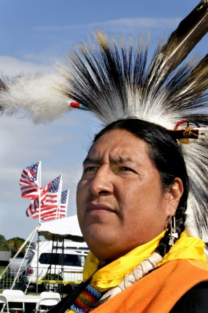 cherokee: Northern Cherokee Indian standing in front of three American flags and a white vehicle  Stock Photo