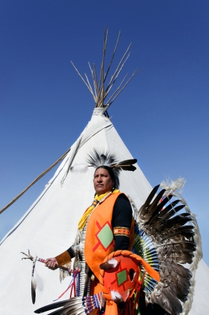 Northern Cherokee indian in full ceremonial dress standing in front of a white tee pee