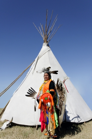 cherokee indian: Proud Northern Cherokee indian man wearing full ceremonial dress and standing in front of a tee pee  Stock Photo
