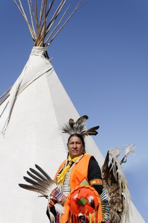 cherokee: Native American Cherokee indian proudly displaying his ceremonial costume and tee pee