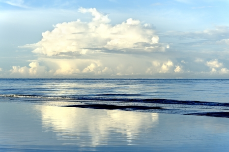Beautiful white puffy clouds reflecting in the water at the sea.