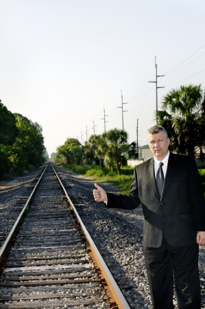 midlife: Business man hitchhiking along a railroad track.