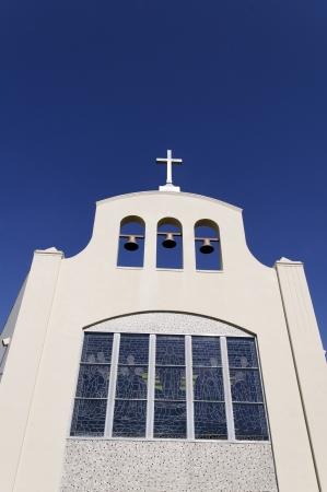 vetrate colorate: Una grande chiesa bianca con vetrate, tre campane e una croce
