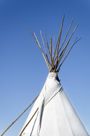 Tee pee with sticks against a clear blue sky.