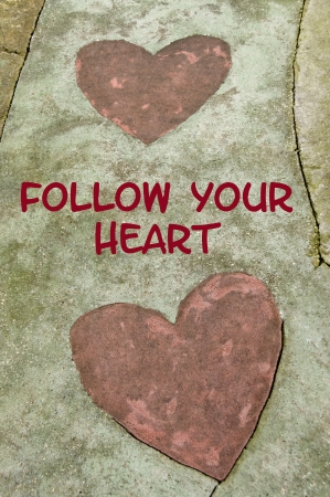 Concrete path with two hearts on it with text that says Follow Your Heart.