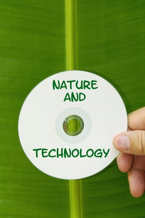 CD disk that says, Nature and Technology being held in front of a green tropical leaf.
