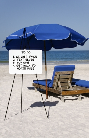 Santa's to do list on a whiteboard in front of a blue umbrella and beach chair at the ocean. photo