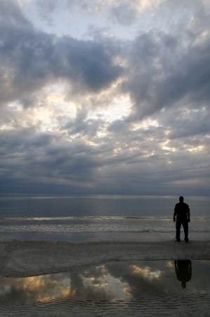 Man standing on the beach with stormy clouds in the sky and clouds reflecting in the water below.