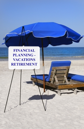 Financial planning sign at the ocean with blue umbrella and lounge chair.