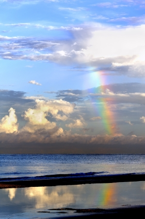 Rainbow coming down from a large fluffy cloud at the ocean. Stock Photo