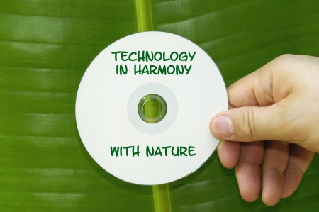 CD disk that says,Technology in Harmony with Nature being held in front of a tropical palm leaf. Stock Photo