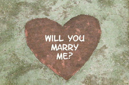 marriage proposal: Concrete slab with a red heart shape in the middle that says,  Stock Photo