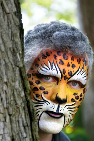 Man with his face painted like a leopard looking out from behind a tree.