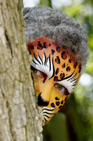 Man with his face painted like a leopard peeking around a tree. Stock Photo - 15785142
