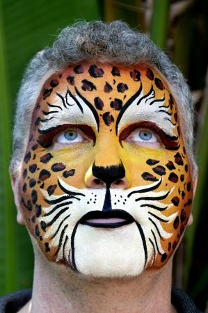 El hombre que está frente está pintado como un leopardo mirando hacia arriba.