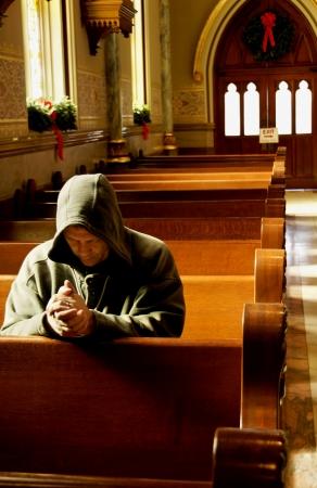 Man praying in a church at Christmas time