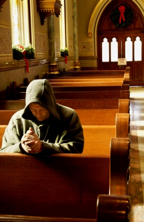 pew: Man praying in a church at Christmas time