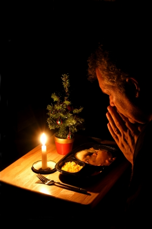 Lonely man praying over a TV dinner at Christmas