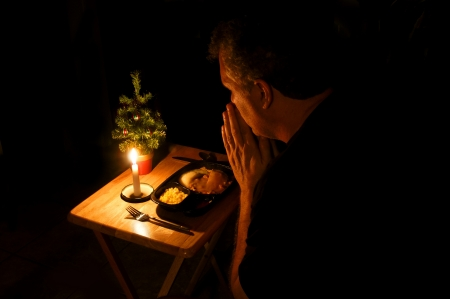 Man praying over a TV dinner at Christmas time  Imagens