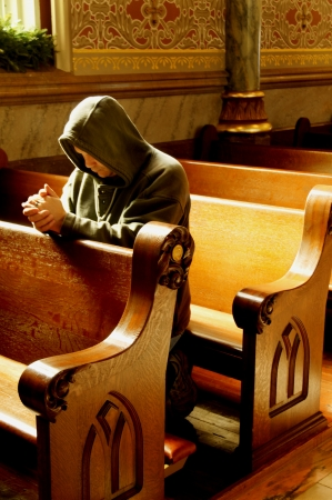 repent: Man praying with his hands folded in a church