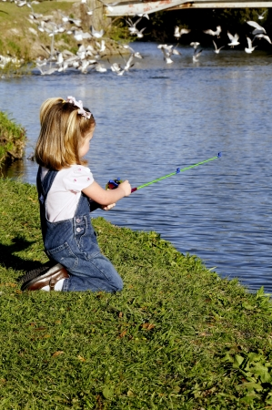 A small girl in overalls fishing at a lake.