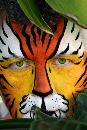 A man whos face is painted like a tiger, peeking behind tropical leaves. photo