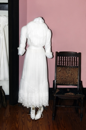 White vintage dress with an antique chair and pink wall.