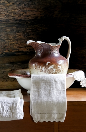Antique wash basin, pitcher and white towel. Stock Photo