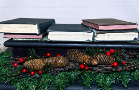 Antique bibles and hymns books with garland and berries at Christmas.