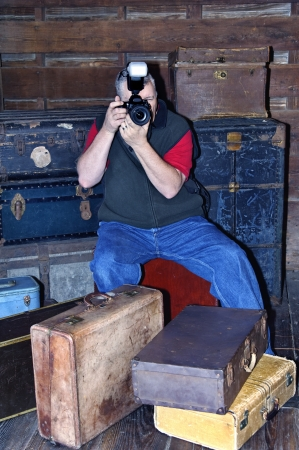 Middle aged man with a camera surrounded by antique suitcases and trunks.