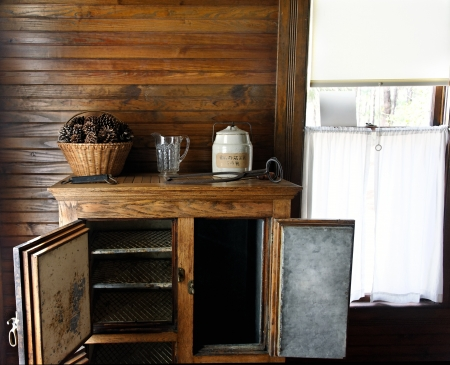 Antique refrigerator with a cookie jar, pitcher, pine cones, and a window
