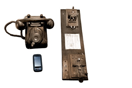 Antique telephone and telegraph plus a modern cell phone with space for text on right side. Stock Photo