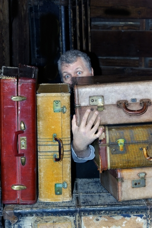 Man looking scared and hiding behind antique suitcases.