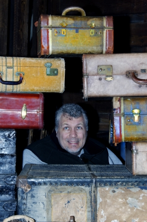 Man with a frightened look on his face in the middle of antique suitcases.