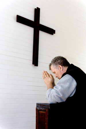 Man praying below a wooden cross in a church. photo