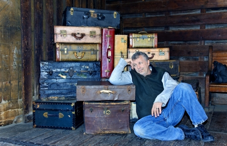 Man waiting at a station with a stack of suitcases in the background. Stock Photo