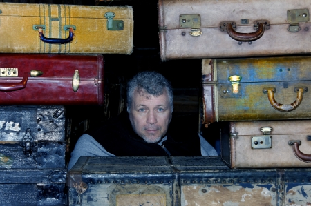 Gray haired man in his fifties surrounded by antique suitcases. photo