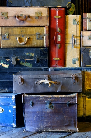 Colorful stack of worn out antique suitcases. Stock Photo