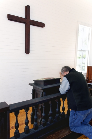 Man kneeling and praying at a church in front of a wooden cross. photo
