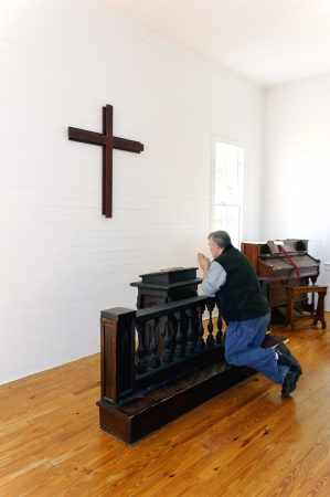 Man kneeling and praying in front of a cross at a church.