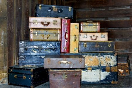 Old antique suitcases stacked up high in a station.