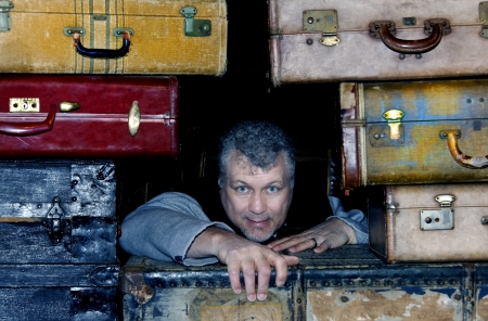 Stressed out middle aged man trying to crawl out of stacked suitcases. Stock Photo